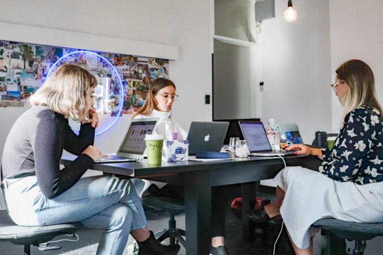 women gathered around computers